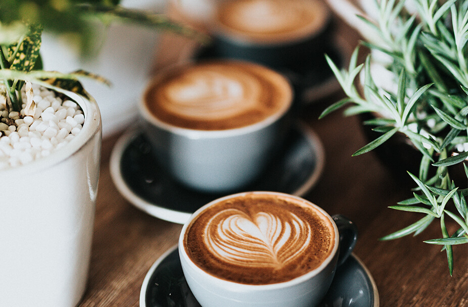 close up photo of a vertical row on three latte coffees with heart shapes in the foam on a wooden table surrounded by plants